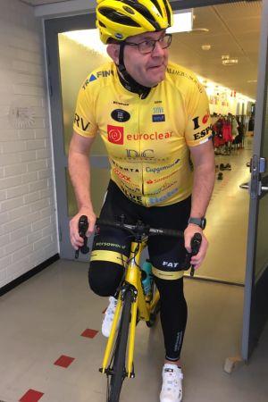 Christer Holmlund står iklädd cykelkläder med en cykel i en korridor.