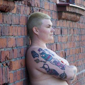 Enni Grundström naken vid en röd tegelvägg.