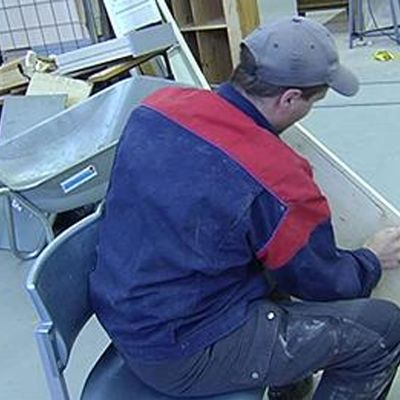 Arbetare sandpapprar en träskiva.