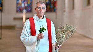 En man i en vit kåpa med röd skarf. Han har gröna kvistar i handen och står i en kyrka.