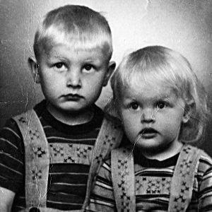 Kaksi pientä poikaa valokuvausstudiossa 1940-luvun lopulla äidin tekemissä shortsihousuissa ja t-paidoissa.