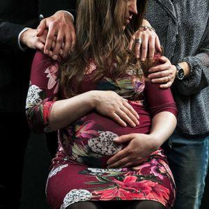 En gravid kvinna sitter på en stol och håller om sin mage.