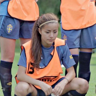Priscilla Burgos står på huk omgiven av sina lagkompisar.