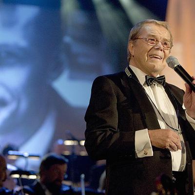 Ikivihreä laulaja ja pianisti Lasse Mårtenson laulelmien ja elokuvamusiikin maagisissa tunnelmissa Tampere-talolla vuonna 2005.