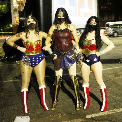 Supersankareiksi pukeutuneet naiset osallistuvat vaaalivalvojaisiin.