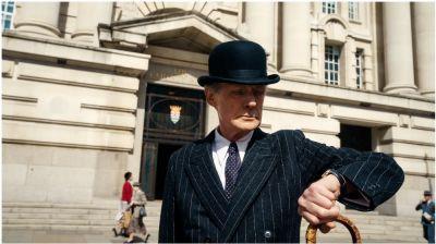 Person med kostym, käpp och plommonstop tittar på sitt armbandsur. Bilden är från en film.
