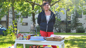 En kvinna i en solig park. Framför henne står ett vitt bord med bakverk på. Kvinnan ler och tittar in i kameran.