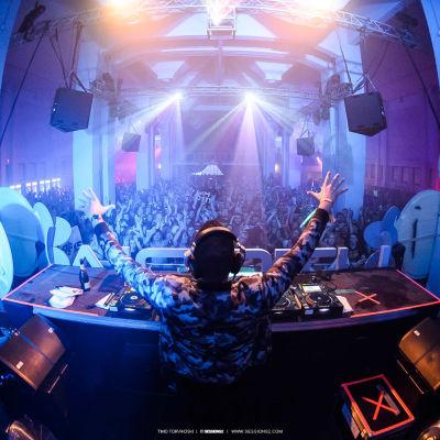DJ seisoo soittopöydän takana kädet ilmassa, edessä näkyy kädet ilmassa juhliva täysi yleisö.