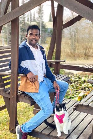 En man sitter i en trädgårdsgunga. En katt i sele sitter bredvid honom.