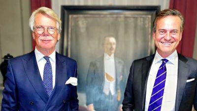 Björn Wahlroos och Mika Ihamuotila står framför en oljemålning. Båda ler rakt in i kameran.