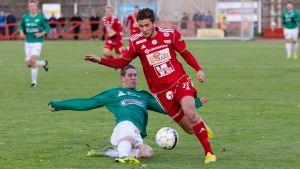 EIF:s Kyle Hoffer glider mot bollen och FC Jazz Kari-Pekka Koivunen.