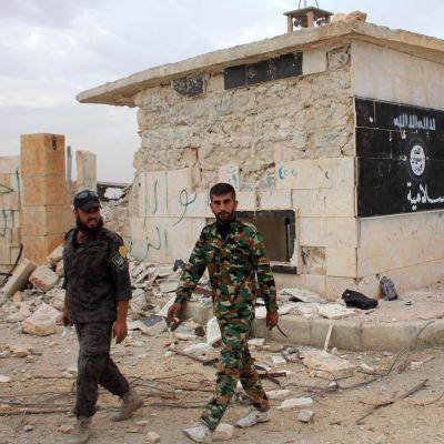 Syyrian hallituksen joukkoihin kuuluvat miehet kävelivät rakennuksen edustalla, johon oli maalattu isisin tunnus Aleppon laitamilla Jabboulin kylässä 24. lokakuuta.