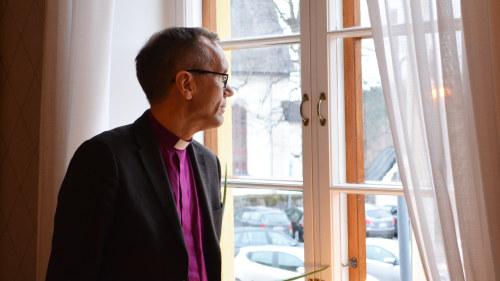 En medelålders man tittar ut genom ett fönster. Han har på sig en lila  skjorta ed7c08b3c1ca7