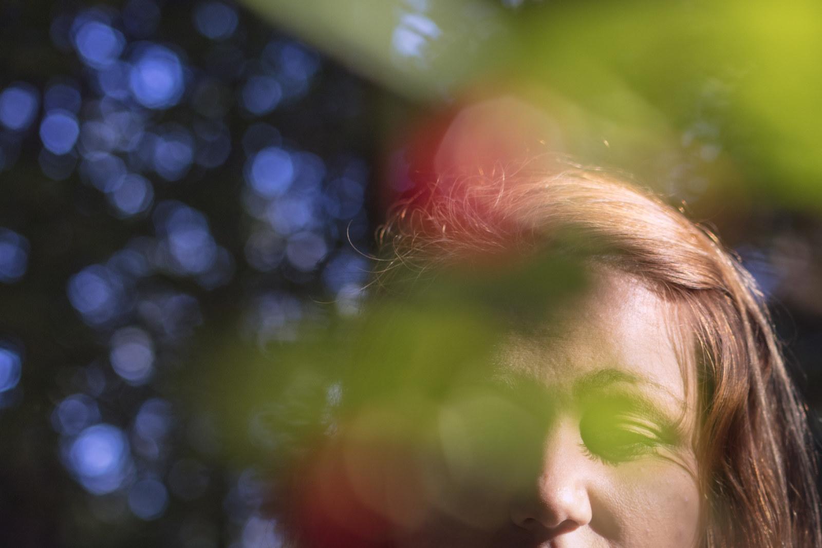 Riia Puska metsässä, etualalla värikkäitä lehtiä eoätarkkana.