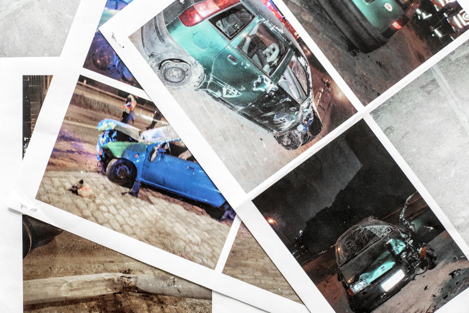 Pöydällä poliisin ottamia valokuvia kolaripaikalta, kuvissa pahoin vaurioitunut auto.