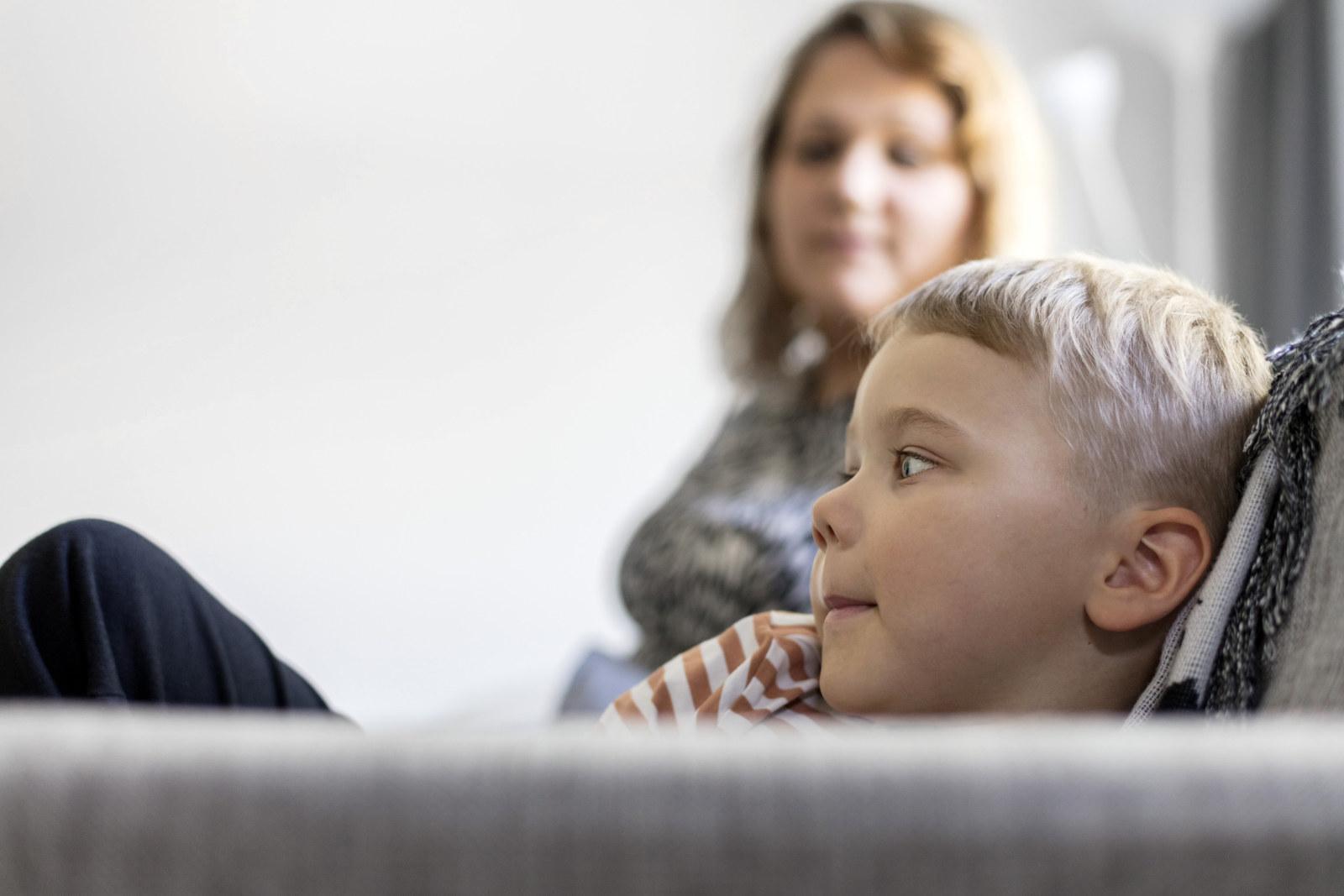 Riia Puska istuu sohvalla yhdessä poikansa kanssa.