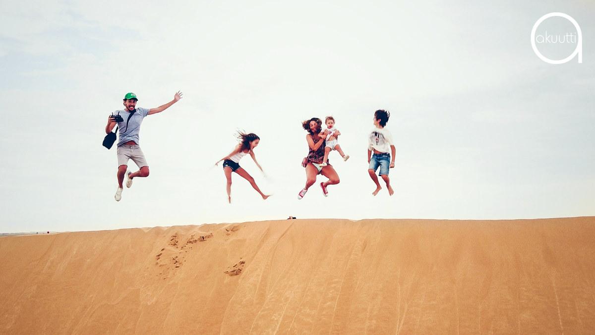 Perhe seisoo hiekkadyynin päällä ja hyppää ilmaan.