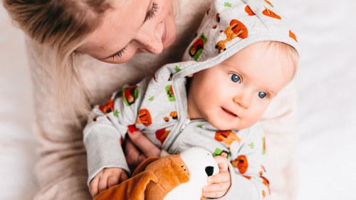 2899764591f3 En mamma med ett barn i famnen. Barnet har på sig kläder ur  moderskapsförpackningen 2017