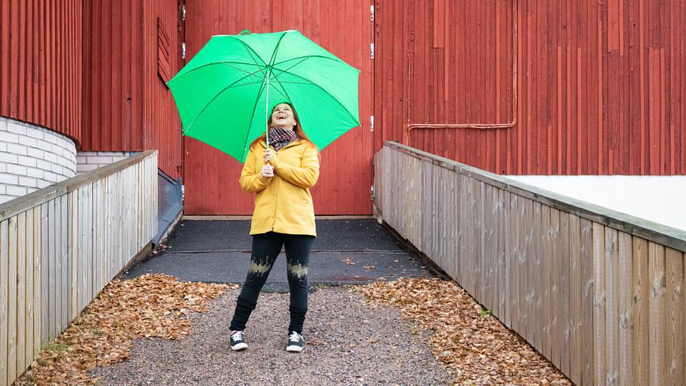 Anne Kassimäki seisoo Navetta-teatterin seinustalla vihreän sateenvarjon alla.