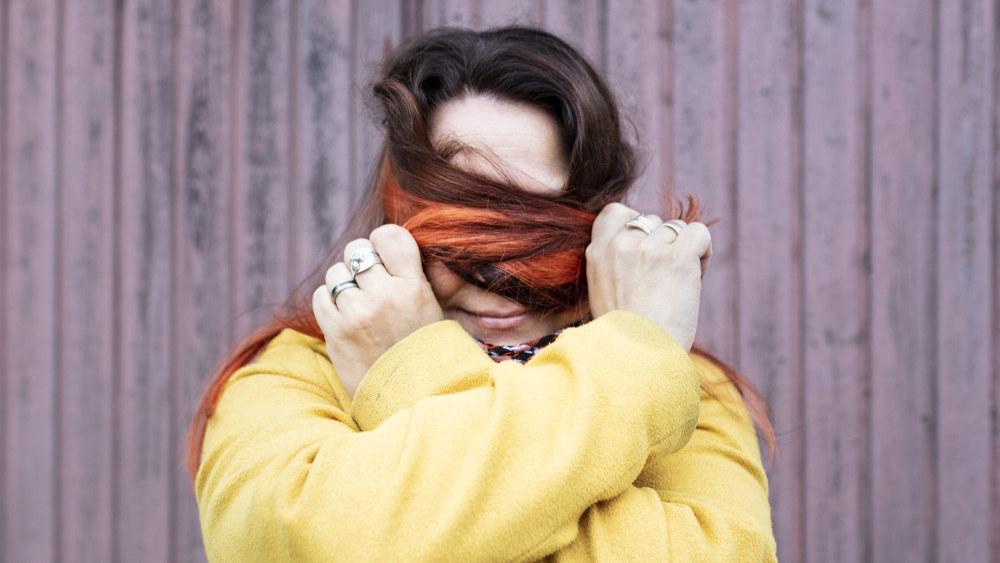 Anne Kassimäki on vetänyt pitkät hiuksensa kasvojensa eteen.