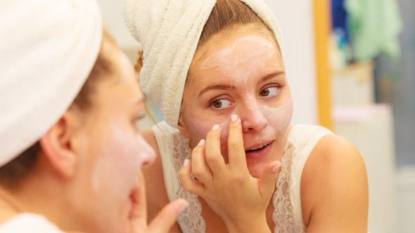 Kvinna applicerar ansiktsmask.