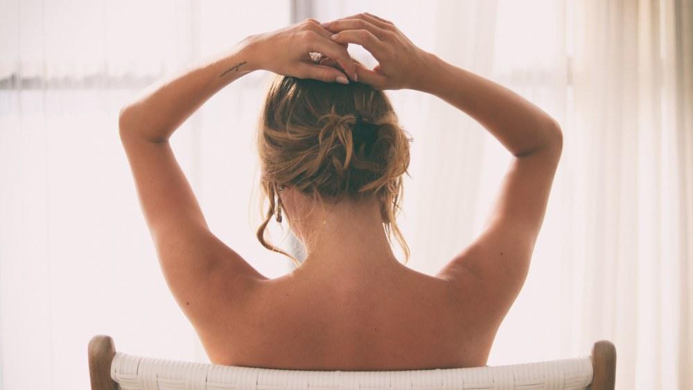 Nainen istuu tuolilla selin, paljas iho näkyy.