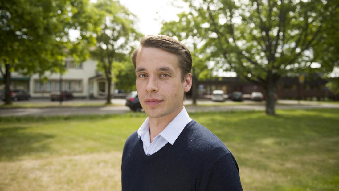 En man iklädd en ljusblå skjorta och en mörkblå tröja. Han är utomhus. I bcecce8187f44