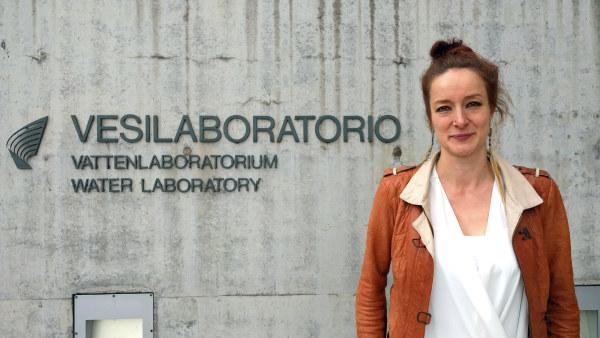 """Julia Talvitie står vid en betongvägg där det står """"Vesilaboratorio, vattenlaboratorium"""". Julia har brun läderjacka och en vit skjorta på sig."""