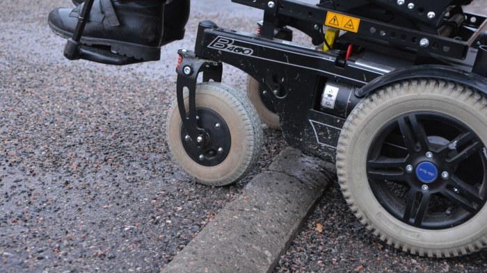Närbild på hjulen som tar sig upp på trottoarkanten