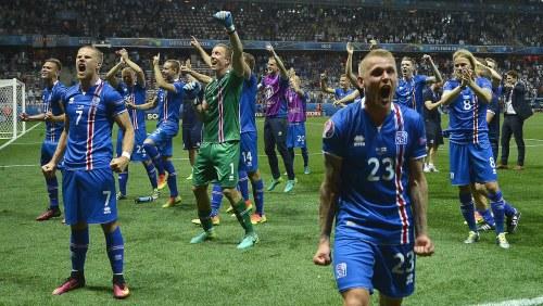 Isländska fotbollspelare i blå-röd-vita tröjor vrålar av glädje pp  fotbollstadium Stade de 205a9417e0925