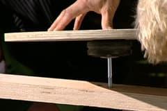 Sätt i en bult från fanerhjulssidan genom lagret i gummihjulet, genom masten och skruva fast det på framsidan