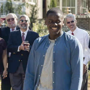 Chris (Daniel Kaluuya) står leende omringad av vita mänskor.