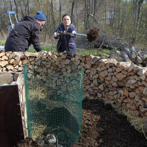 Owe Salmela och Camilla Forsén-Ström fyller nyckelhålsodling med gödsel