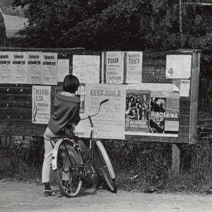 Flicka och cykel framför annonstavla