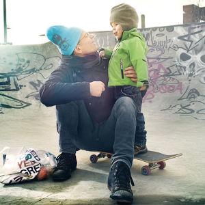 Isä halaa pientä poikaansa skeittirampilla.