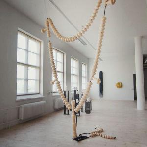 Interiör från en utställning i konstcentret Antares. Ett band bestående av stora träpärlor hänger från taket.
