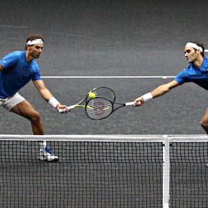 Nadal och Federer på samma sida nätet, kämpar om bollen