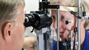 Hannu Uusitalo tutkii potilaan silmiä.