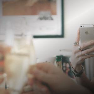 Några händer som håller i glas skålar medan en hand håller i en smarttelefon och fotar händelsen.