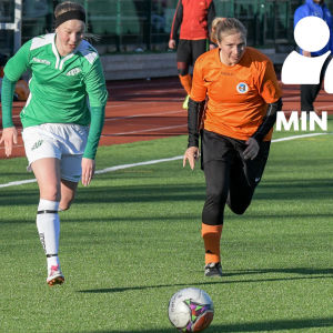 Två kvinnliga fotbollsspelar, den ena i grönvitt och den andra i svartorange, springer efter en boll på grönt konstgräs.