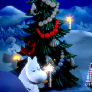 Mumintrollet står ute vid en pyntad julgran och håller i ett ljus, bredvid står hans föräldrar insvepta i en filt.