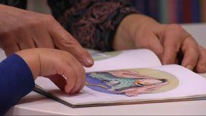 Barnbarn med mormor läser bok.