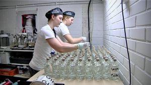 Marianne Aheinen och Juulia Rinta sätter korkar på flaskorna.