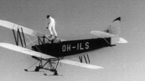 Ilma-akrobaatti seisoo lentokoneen siivellä lentonäytöksessä Helsingin Kaivopuistossa 1951.