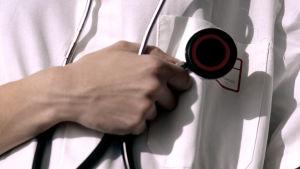 En läkare som håller i ett stetoskop.