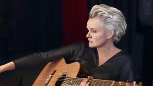 Eva Dahlgren med akustisk gitarr i famnen.