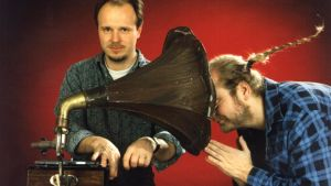 mies pyörittää grammaria, toinen kuuntelee tukka putkella äänitorvesta kuuluvaa ääntä