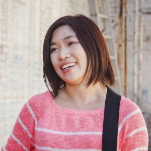 Nainen hymyilee lähikuvassa, taustalla tiiliseinää