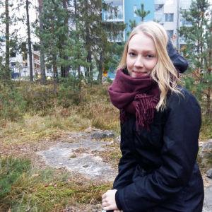 Karoliina Tolkki istuu metsikössä kivellä