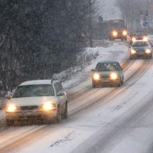 Bilar och en buss kör på hal och snöig väg.